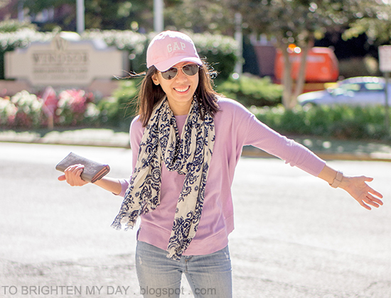 pink cap, navy floral scarf, lilac purple sweater, gray taupe clutch, light wash jeans, oversized watch