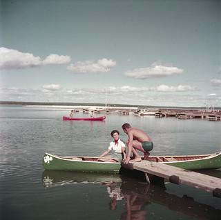 Man on a dock, woman in a canoe on Lake Waskesiu, Prince Albert National Park, Saskatchewan / Homme sur le quai et femme dans un canot, lac Waskesiu, parc national de Prince Albert (Saskatchewan)