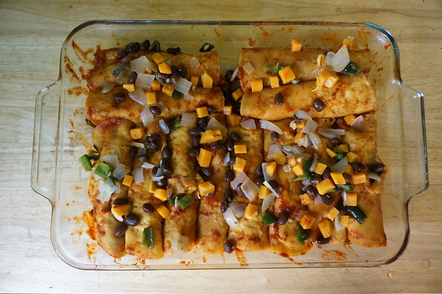 A full pan of sweet potato-black bean enchiladas, scattered with spare filling, just needing some sauce and a final sprinkling of cheese before going to the oven