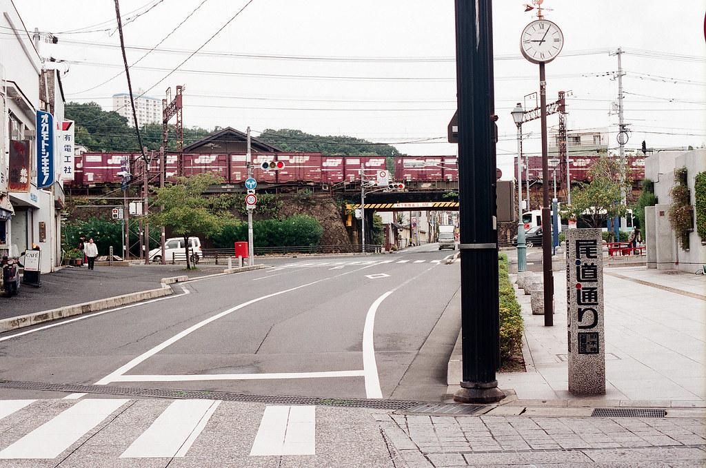 尾道 おのみち Onomichi, Hiroshima 2015/08/30 剛好一輛貨運列車經過,和路旁的時間一起入鏡。  Nikon FM2 / 50mm FUJI X-TRA ISO400 Photo by Toomore