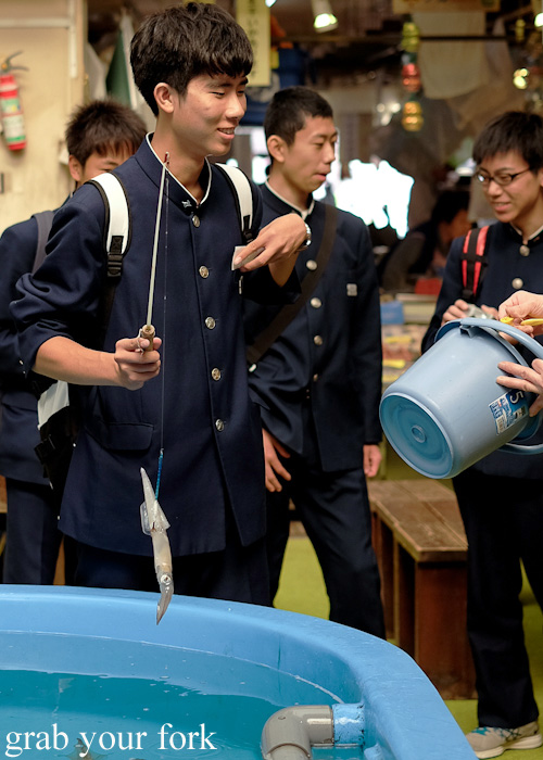 School kids win the squid fishing game at Hakodate Morning Market, Japan