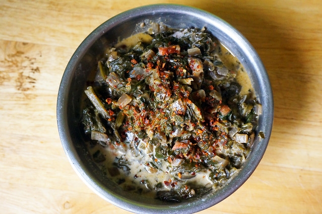 A bowlful of Coconut creamed spinach sitting on a plain wood countertop