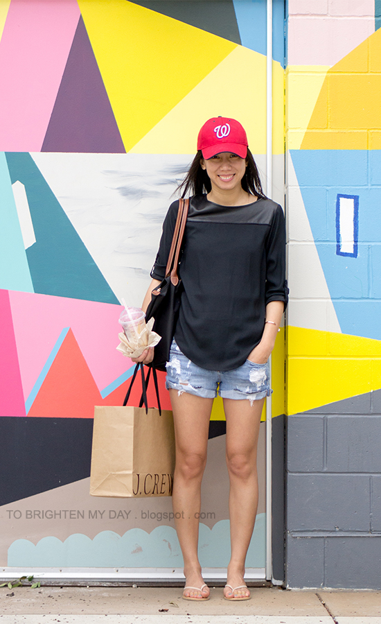 red cap, black faux leather yoke top, distressed shorts, flip flops