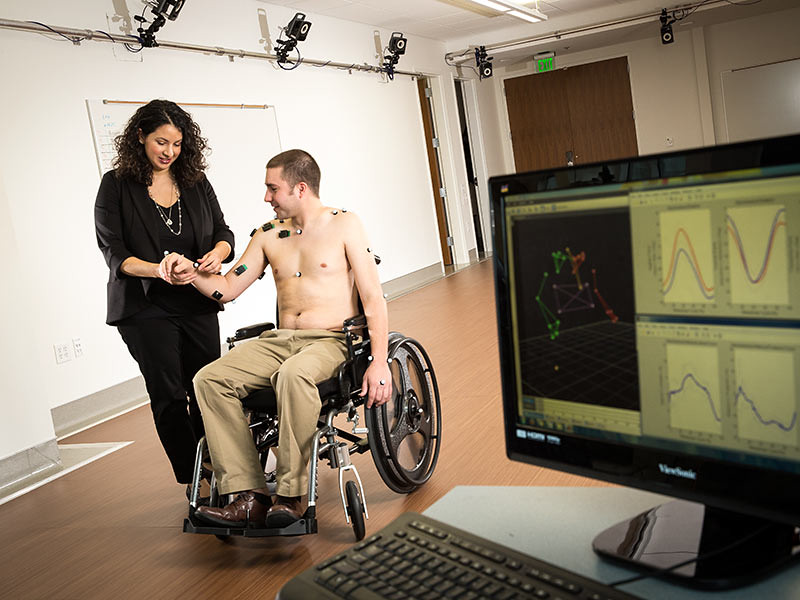 Assistant Professor Brooke Slavens prepares for motion capture and muscle activity assessment to investigate the biomechanics of manual wheelchair mobility with a geared wheel system.  She is placing a reflective marker on the wrist of a human subject, while he is seated in a manual wheelchair.