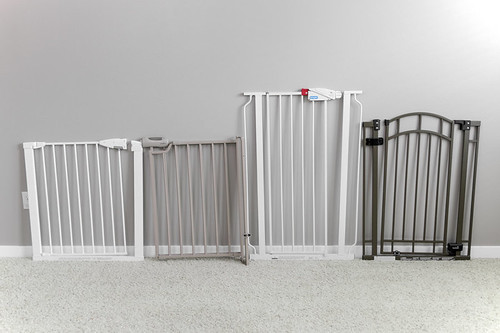Lineup of four baby gates on carpet