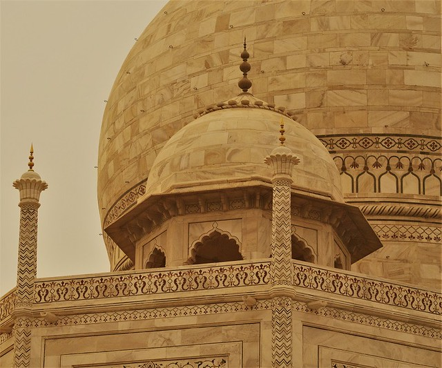 close up of one of the small taj mahal domes with the big one looming in the bachground