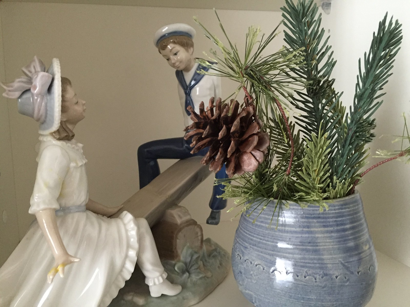bits of Christmas greenery beside a Lladro figurine