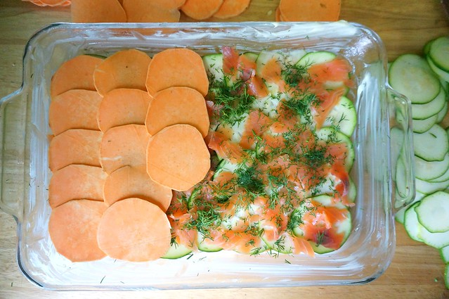 The same baking dish as before, with a similar half-layer of sweet potatoes, only this time they're half-covering a layer of salmon and dill. You can see between the bits of salmon to the pale green zucchini in the layer below. It's like a glorious mosaic, half-tiled over with pavers.