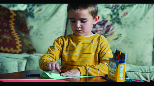 A boy coloring on a piece of paper