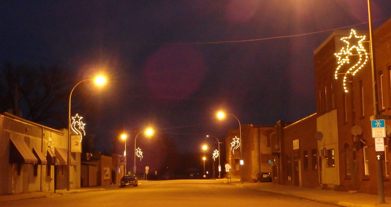 lighted star decorations on both sides of a quiet street