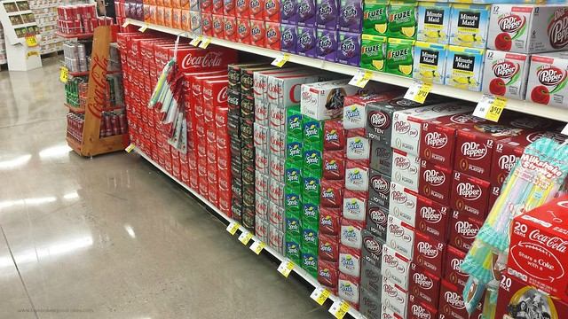 A grocery store isle with soft drinks on the shelves.