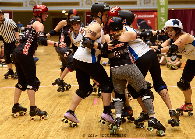 Santa Cruz's jammer, Frisky Biscuits assists with defending against Demolition City's Hurtz Donut.