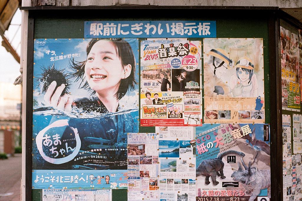 """小海女 能年玲奈 岩手 久慈(Kuji) 2015/08/08 車站前的佈告欄,小海女的海報。  在東日本時,從八戶轉車繼續前往岩手久慈,搭了快兩個小時的車,最後終於抵達。在車站前的佈告欄,可以看到小海女的海報,應該說久慈這個小鎮到處都是小海女相關的訊息。一部日劇就帶動一個偏遠城市的觀光,很厲害!  Nikon FM2 / 50mm Kodak ColorPlus ISO200  <a href=""""http://blog.toomore.net/2015/08/blog-post.html"""" rel=""""noreferrer nofollow"""">blog.toomore.net/2015/08/blog-post.html</a> Photo by Toomore"""