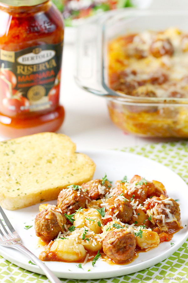 Gnocchi and Meatball Bake on a white plate with garlic bread and a fork.