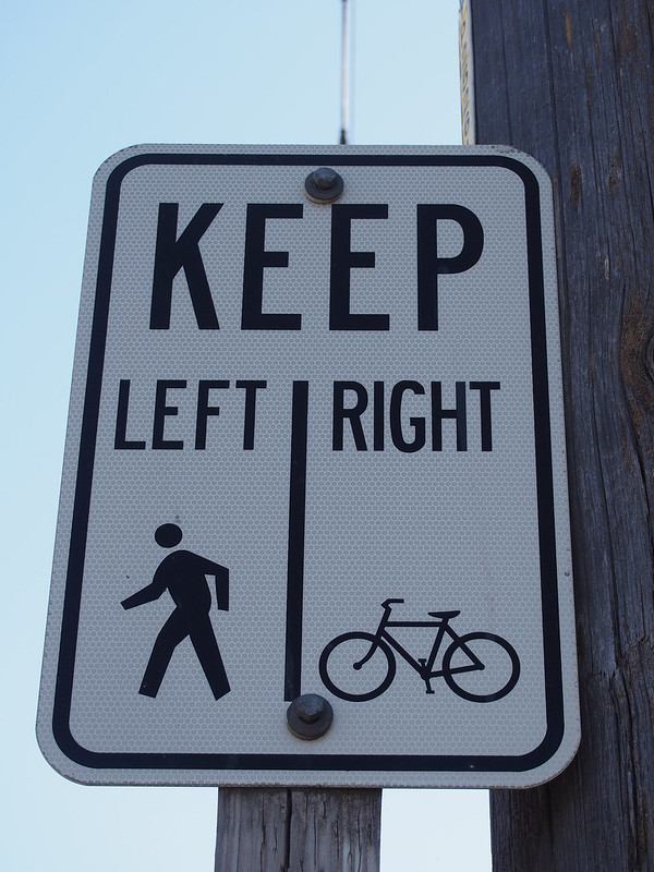 Incorrect Bike Lane Sign: The LEFT directs pedestrians to walk into the 'regular' bike lane on the pavement, while the RIGHT directs cyclists to ride on the sidewalk.