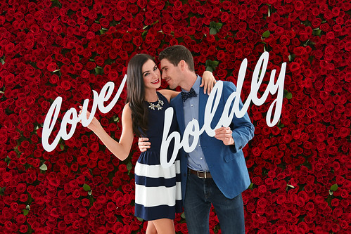 man and woman couple in front of red rose bloom flower wall and love boldly sign