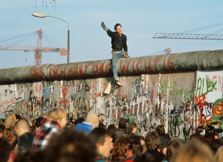 A man sitting on Berlin Wall during its fall