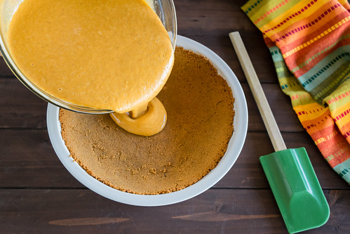 pouring the pumpkin filling into the crust