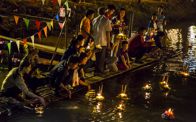 Thai people setting their candle-lit krathongs in the Ping river at night during Loy Krathong 2015-103