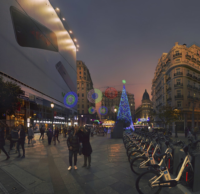 Movistar smartphone advertisement, BiciMAD bicycles, and Christmas decorations on Calle Montera, Madrid (2015)