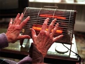 Una dona gran intenta escalfar-se amb una senzilla estufa, a Perth (Escòcia) / Ninian Reid