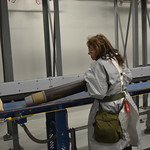 An ordnance technician tilts a fiberboard tube to remove an agent-monitored 105mm munition, in a process known as Baseline Reconfiguration. The munition is then rolled back onto the conveyor to be inspected for any discoloration or damage in the Enhanced Reconfiguration Building at the Pueblo plant.