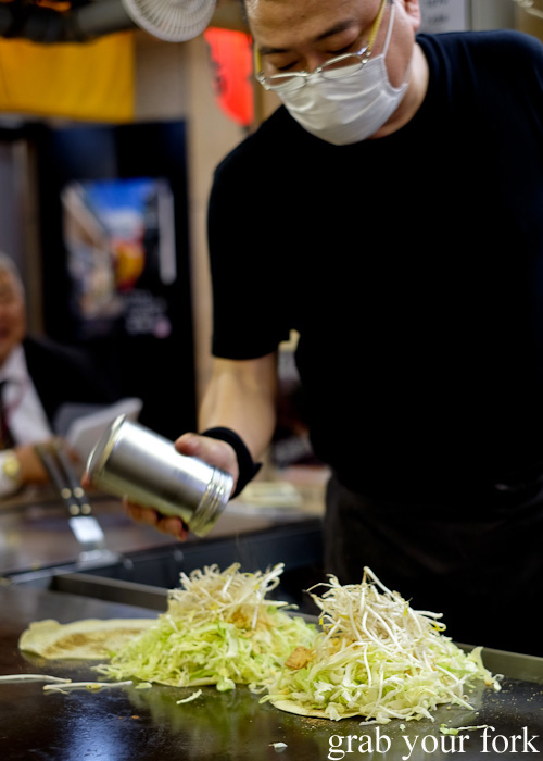 Layering cabbage and bean sprouts for Hiroshima-style okonomiyaki at Okonomimura, Hiroshima