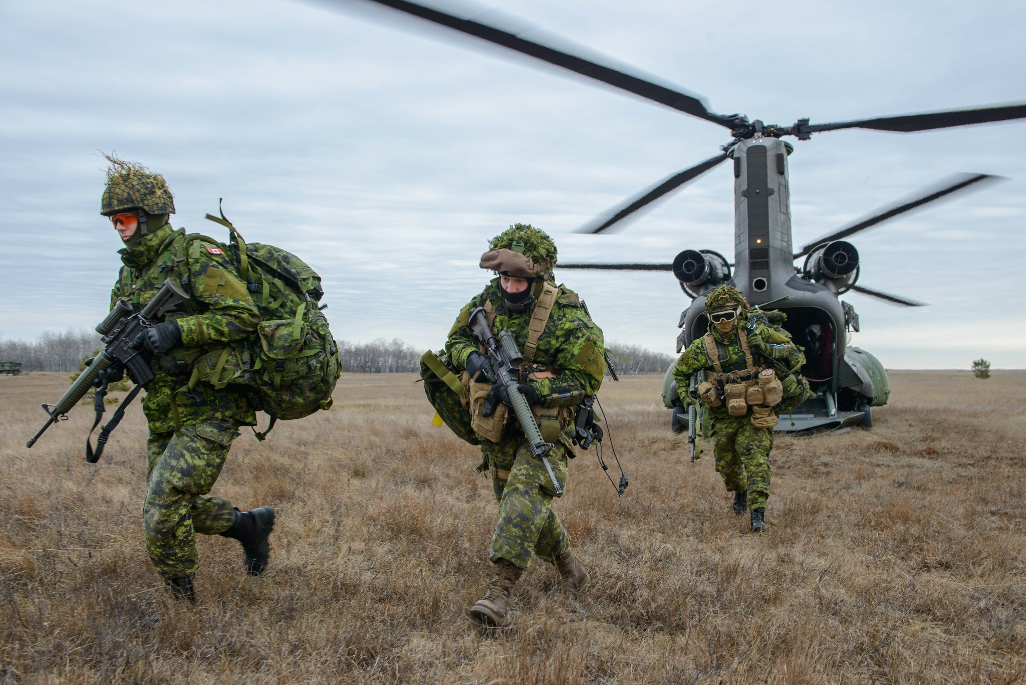 Members of 1st Regiment Royal Canadian Horse Artillery disembark a CH-147F Chinook helicopter from 450 Tactical Helicopter Squadron as part of Exercise CHINOOK GUNNER at CFB Shilo, Manitoba