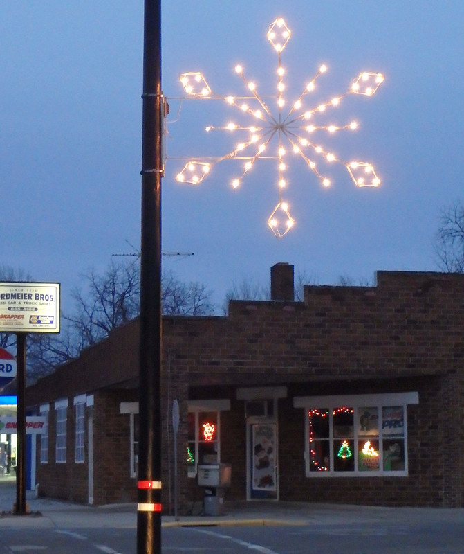 lighted snowflake on a pole in front of a business with lighted decorations in the windows