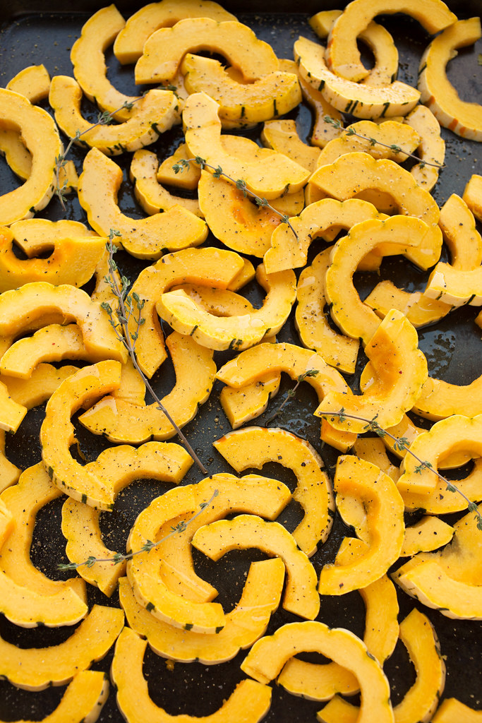 delicata squash rings on baking sheet with thyme