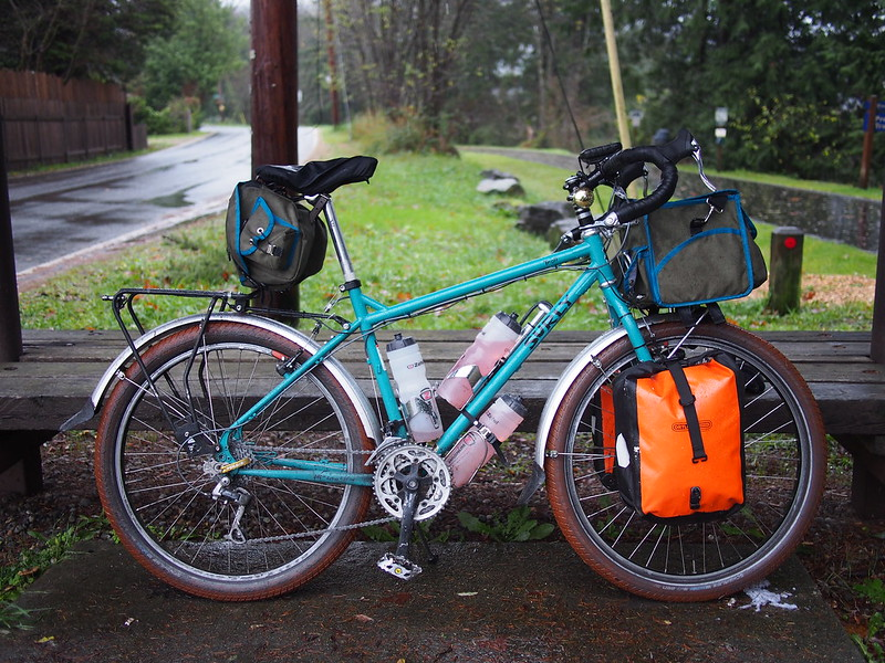 Beyond the Horizon: Front Loading: I experimented with a different load configuration this time, with almost all of the gear up front.  It handled very well, and climbing out of the saddle was easy.  The 'center of gravity shift' that freaks me out about steep grades (which can easily result in wheelies) was significantly reduced with this loading.  The bike tended to oversteer a little, but that's easier than trying to wrestle a bike whose tail is being swung back and forth by a heavy rear load.