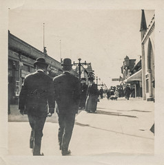 Men in bowler hats walking down a sidewalk