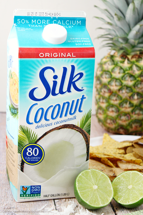 A carton of Silk Coconut with two limes.
