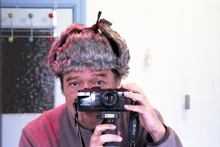reflected self-portrait with Minolta Riva Zoom 105i camera and new hat
