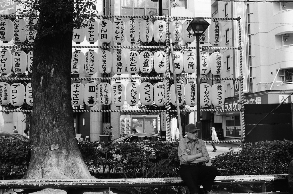 池袋西口公園 東京 Tokyo / Kodak TRI-X 400 / Nikon FM2 2015/10/04 在準備離開池袋西口公園的市集前,我開始將拍攝觀察的目標從場內移轉到場外,其實我 2014/09 的時候來過池袋,我記得這一串的燈籠,所以我趕緊看看燈籠附近有沒有可以拍的畫面,果然有一個阿伯可以入鏡,拍下這張!不過這裡卻發現相機的測光好像快沒電了!  Nikon FM2 Nikon AI AF Nikkor 35mm F/2D Kodak TRI-X 400 / 400TX 1274-0018 Photo by Toomore