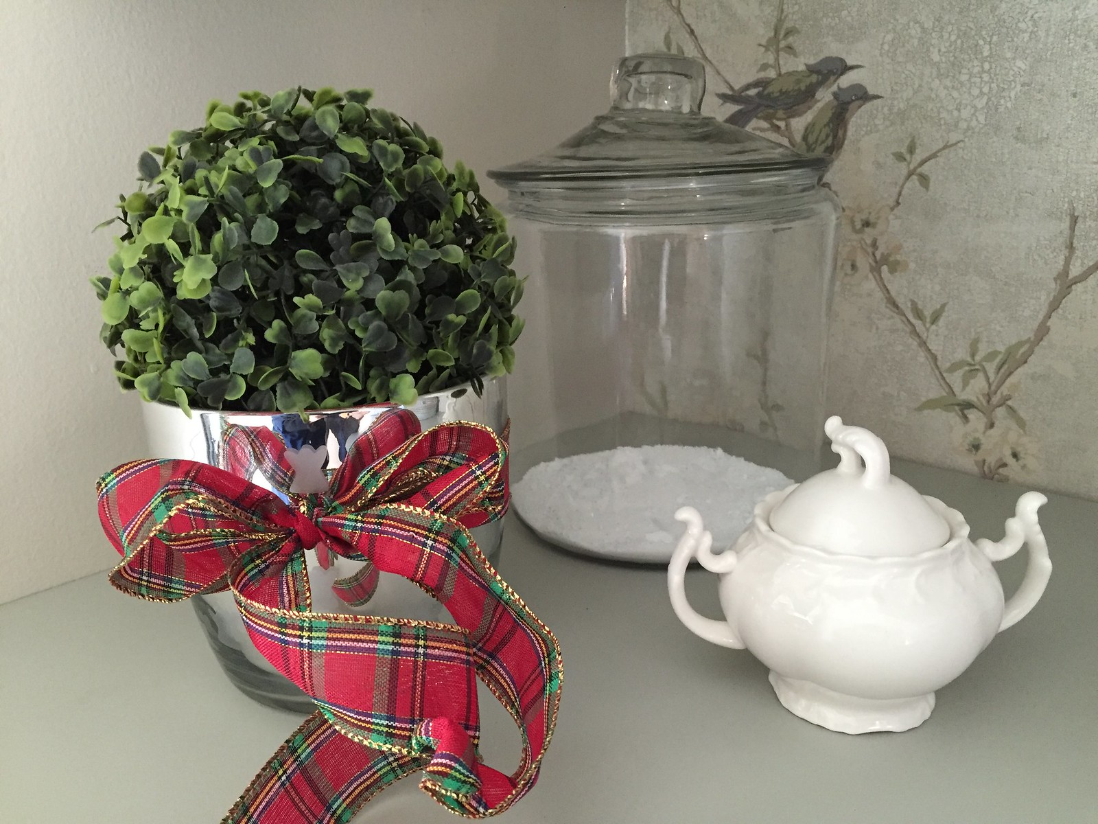 boxwood ball with christmas plaid ribbon in a laundry room