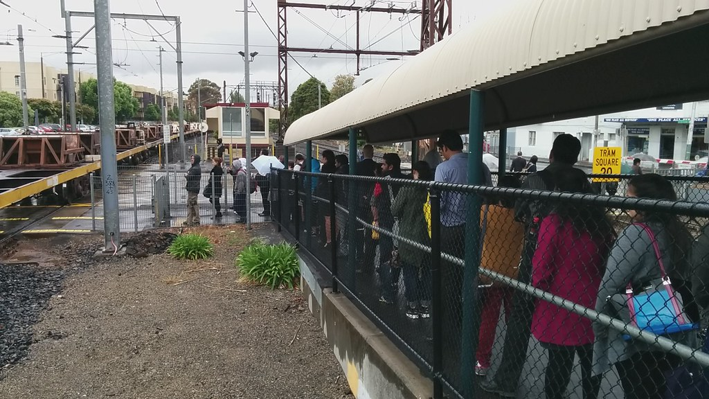 Glenhuntly station: passengers waiting for passing freight train