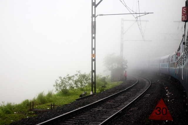 track5, dense white fog is seen to the left side of the photo, green shrubbery is on the ground and a triangular sign with 30 is on the ground