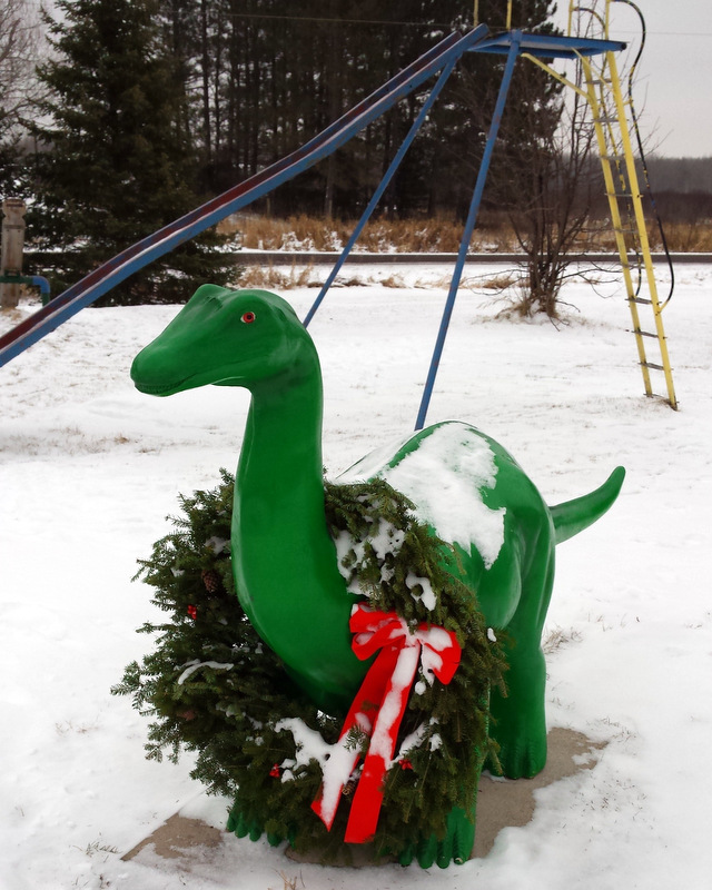 green apatosaurus with a wreath around its neck, in front of a snow-covered slide