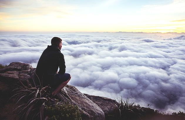 Hombre mirando sobre nubes