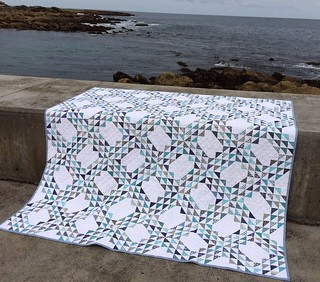 Ocean Waves quilt in front of very small ocean waves. Pattern is by Denyse Schmidt from her book Modern Quilts, Traditional Inspiration though I made it larger than the pattern. This has 100 blocks, 1200 half square triangles & is 80 inches square.