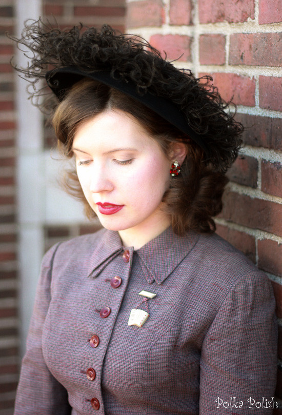 1950s suit with rhinestone earrings, accordion novelty brooch, and ostrich feather hat