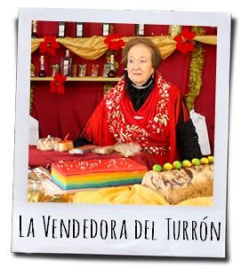 Een in typische kleding gehulde verkoopster van Turrón op de kerstmarkt in Jijona