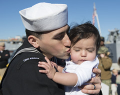 Sailor kisses his newborn child after completing a 7-month deployment aboard USS Essex.