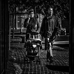 Strolling With Her Child As Man Walks By On A Mission, Martin Luther King Jr. Avenue, Historic Anacostia, Washington, DC
