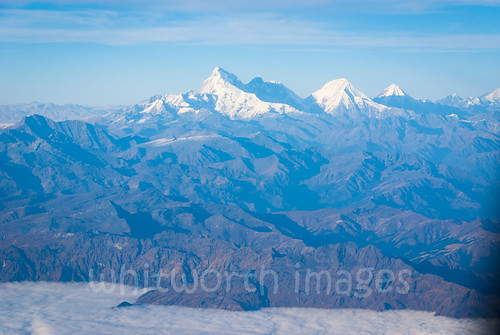 view peaks rugged range alps himalaya mountains himalayas aerial bhutan clouds blue flight travel distant drukair highest high jhomolhari snow chomolhari above wild landscape over asia nepal flying sky tallest snowcapped scenic scene tall