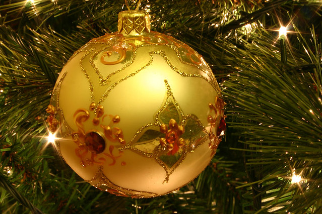 Golden bauble decorating a Christmas tree. By Kris De Curtis. Photo courtesy Wikimedia/ Creative Commons