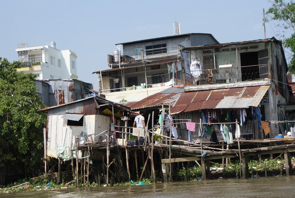 Ces maisons sur l'eau du delta du Mékong sont habitées par les habitant les plus pauvres. En arrière plan des maisons modernes et salubres.