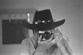 reflected self-portrait with Praktica MTL 3 camera and wide-brimmed hat