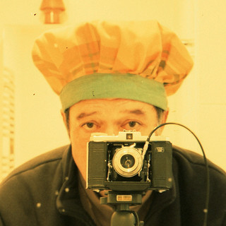 reflected self-portrait with Nettar 517/16 camera and mob cap (square crop)